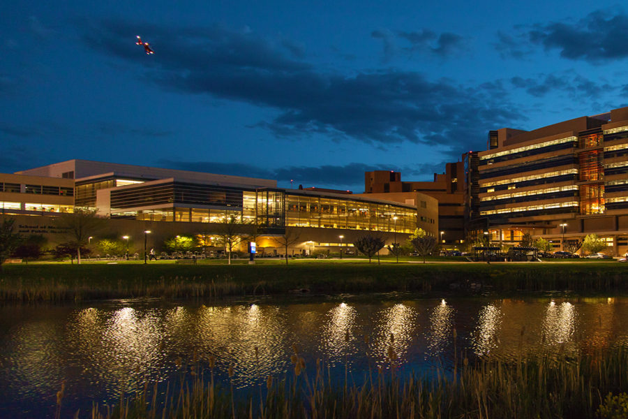 Nighttime photograph of UW-Madison SMPH buildings from across the lagoon