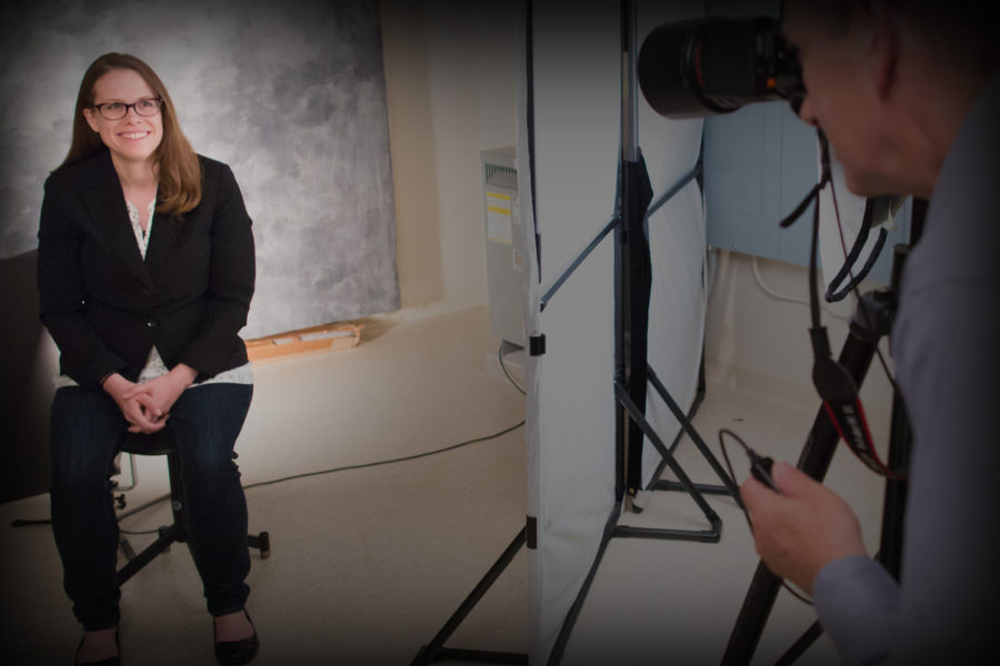 Photographer behind camera during a photo shoot with woman smiling for camera
