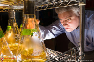 male scientist in background reaches for lab beaker, which has a yellowish liquid partially filling it