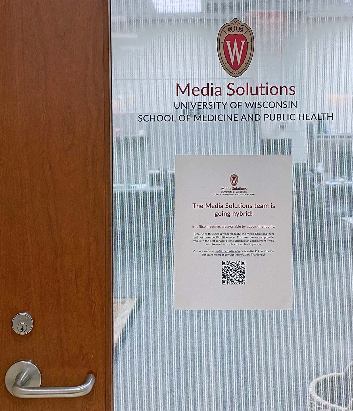 Front door sign reads: The Media Solutions team is going hybrid! In-office meetings are available by appointment only.